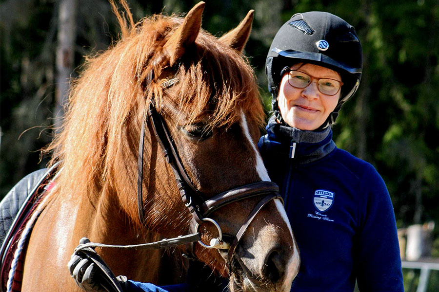hevonen, hymyilevä ratsastaja seisoo hevosen vierellä